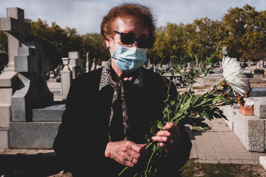 Una mujer deja flores en la tumba de sus familiares en el Cementerio de la Almudena, Madrid.